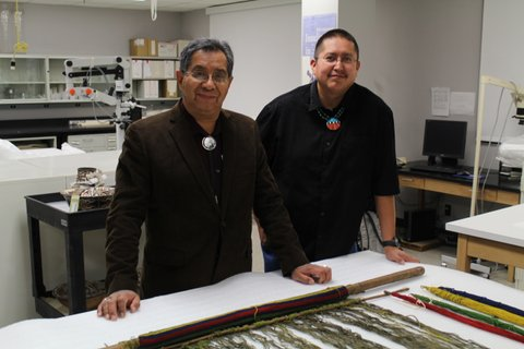 Zuni Indian guests Octavius Seowtewa and Curtis Quam stand next to a loom donated to the Smithsonian in 1886 by Zuni artist We'wha, a transgender woman known for her weaving skills.