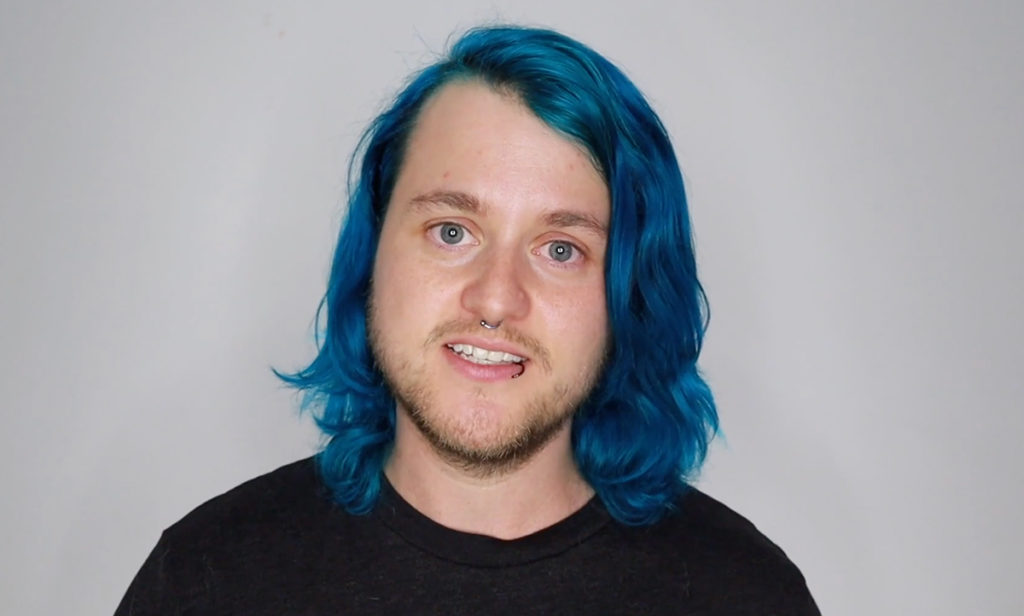 A close-up of Chase Ross, a trans man with long blue hair
