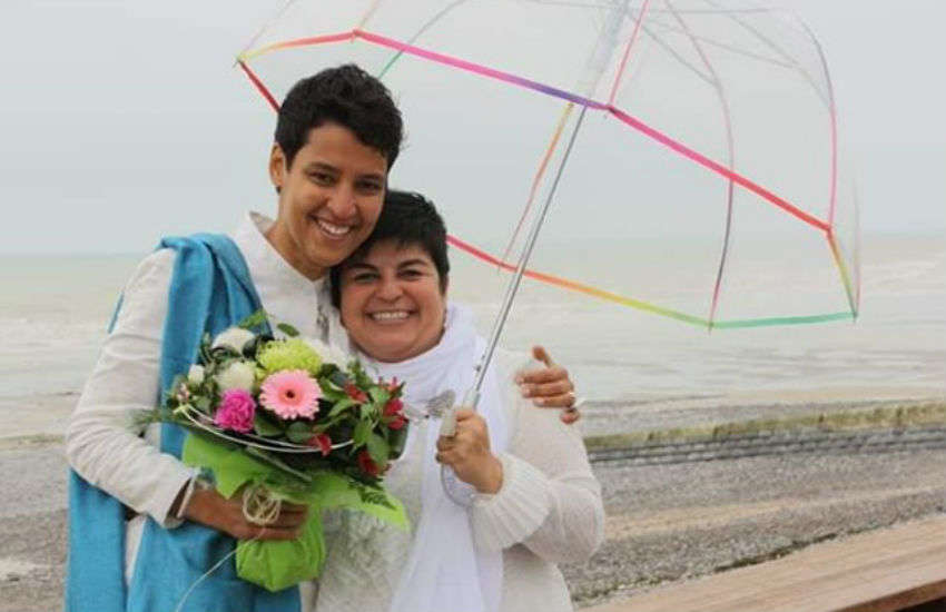 Mariama Diallo (L) and Christina Palma (R) under a rainbow umbrella holding flowers