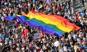 Large crowd of people march under a giant rainbow LGBT glag