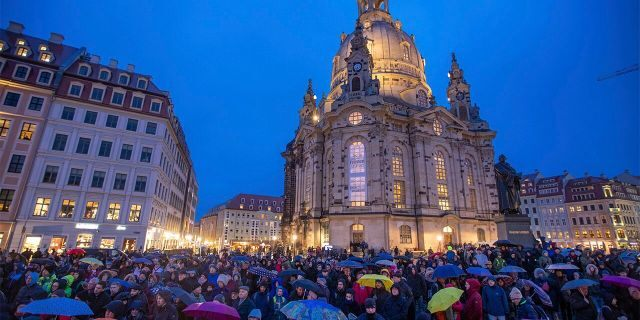 People gather in front of the Frauenkirche for the opening event of the human chain on the occasion of the 75th anniversary of the destruction of Dresden in the Second World War, in Dresden, Germany, Thursday. (Jens B'ttner/dpa via AP)