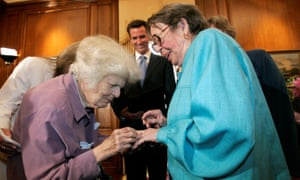 Del Martin and Phyllis Lyon exchange rings during their wedding ceremony officiated by Gavin Newsom (center) at City Hall in San Francisco.