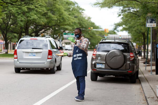 An election worker in Detroit instructing drivers where to drop off their ballots.