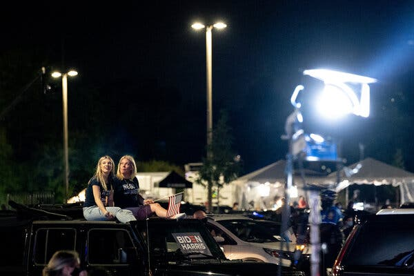 People sat in a parking lot watching the convention livestream outside the Chase Center in Wilmington, Del., where Joseph R. Biden Jr. accepted the Democratic nomination.