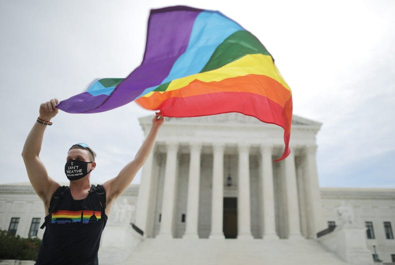 WASHINGTON, DC - JUNE 15: Joseph Fons holding a Pride Flag in front of the U.S. Supreme Court building after the court ruled that LGBTQ people can not be disciplined or fired based on their sexual orientation, Washington, DC, June 15, 2020. With Chief Justice John Roberts and Justice Neil Gorsuch joining the Democratic appointees, the court ruled 6-3 that the Civil Rights Act of 1964 bans bias based on sexual orientation or gender identity. Fons is wearing a Black Lives Matter mask with the words 'I Can't Breathe', as a precaution against COVID-19.