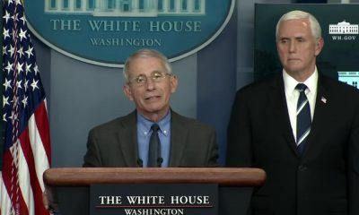Anthony Fauci speaking at a lecturn while Mike Pence glares over his shoulder