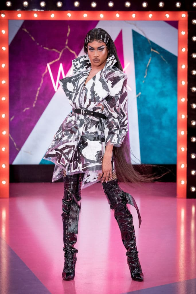 Tayce wearing a laminated black and white coat, waist belt and high black boots