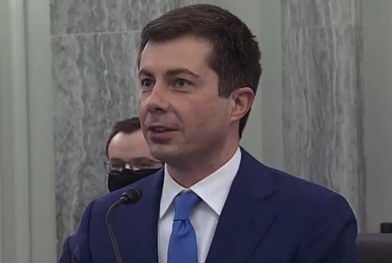 Pete Buttigieg at the Senate confirmation hearing with his husband Chasten behind him