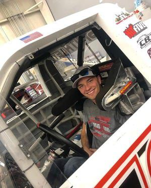 Devon Rouse sits in the drivers seat of his race car.