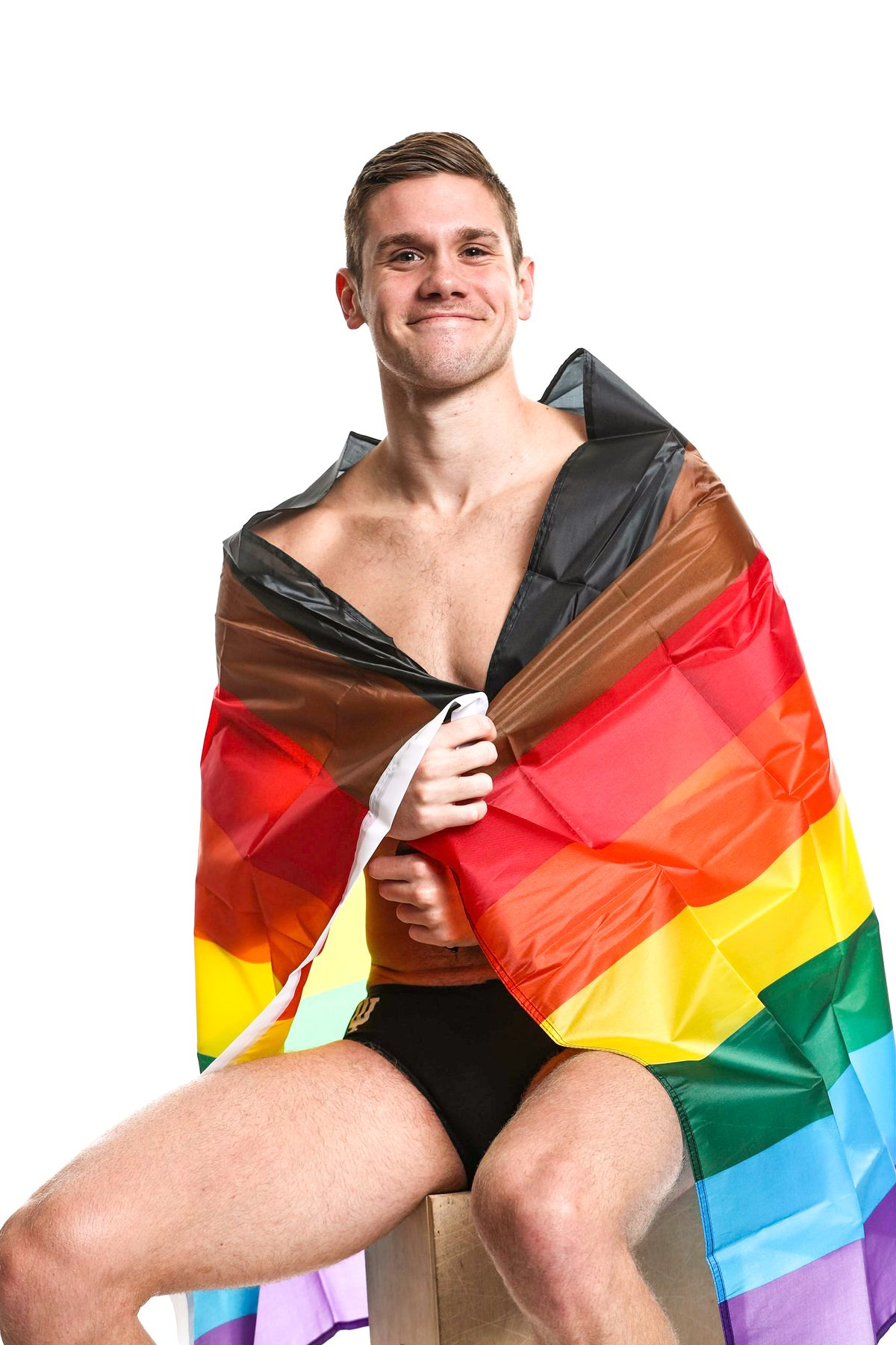 Thomas Vanderbrook wrapped in a rainbow flag.