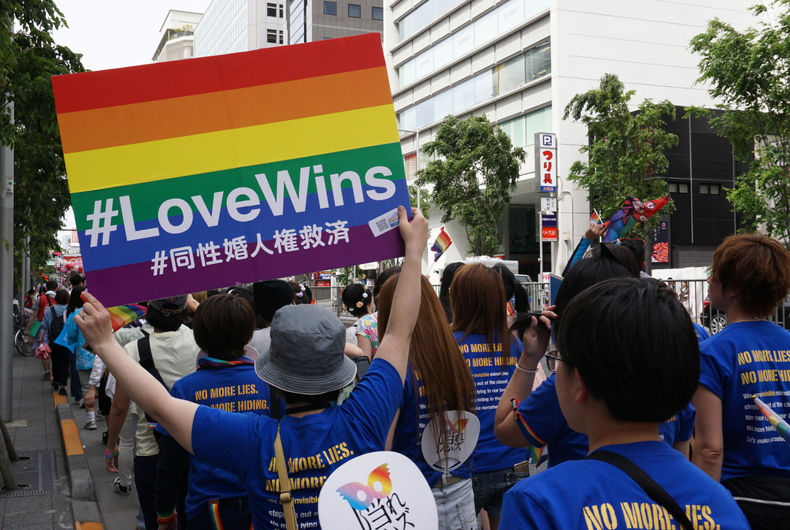 Person holding rainbow poster Love Wins for same-sex marriage rights among people marching in the Tokyo Rainbow Pride (TRP) Parade 2016 in Shibuya, Tokyo, Japan.