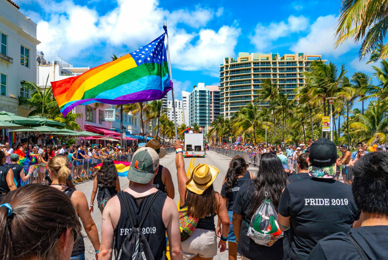 MIAMI, FLORIDA / UNITED STATES - APRIL 9, 2019: Pride Parade on Ocean Drive in Miami Beach. An American LGBTQ Pride flag is being waved.